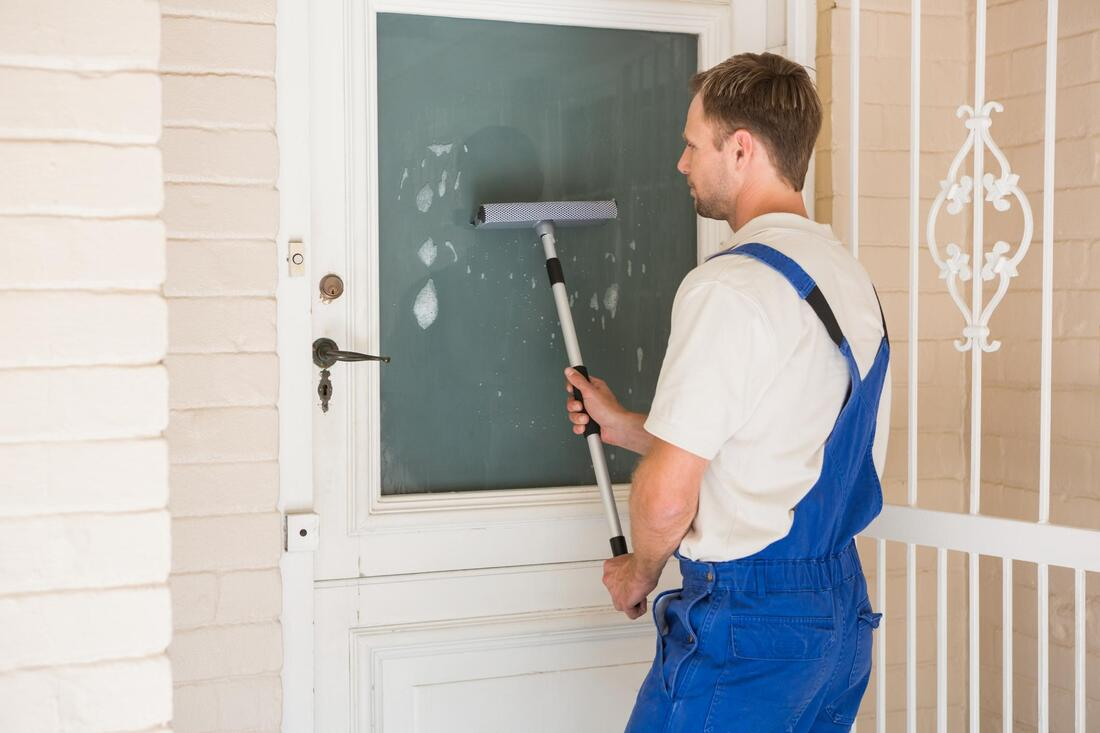 Image of man cleaning a window on a door.