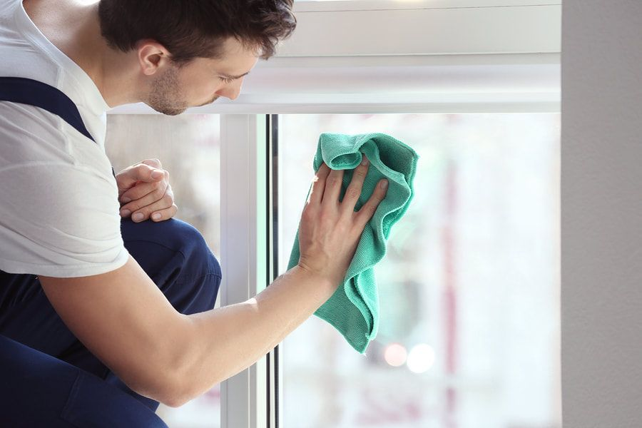 Man wiping a window with a micro fiber towel.